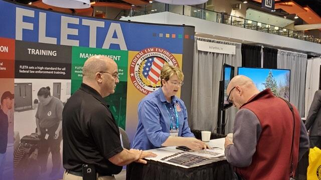 Christiana Halsey and Joe Collins speak with a visitor to the FLETA Booth