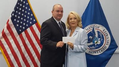 FLETA Office of Accreditation Joe Collins (left) presents FLETC Director Connie Patrick with a retirement gift