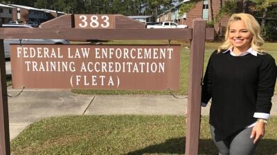 Crystal Johnson stands next to the Federal Law Enforcementing Training Accrecitation FLETA sign