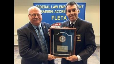 Dr. Gary Mitchell receives his retirement plaque from FLETA Board Chair Brian Peters