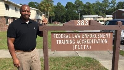 Sean Jones, FLETA Staff Assistant, stands next to the Federal Law Enforcement Training Accreditation (FLETA) sign