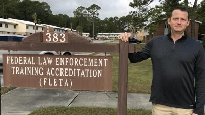 JJ Hensley stands next to the Federal Law Enforcement Training Accreditation Offic of Accreditation sign