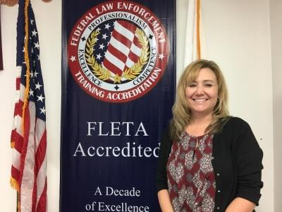 Jennifer Kasper standing next to the FLETA Accredited banner in the Office of Accreditation