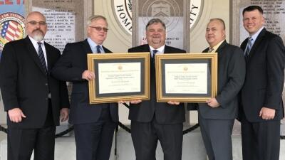 Members from the United States Secret Service hold the two FLETA Accreditation Certificates